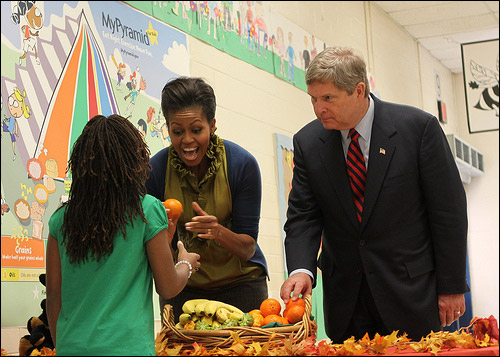 First Lady Michelle Obama and Secretary of Agriculture Tom Vilsack pass out fresh fruit to students at Hollin Meadows Elementary School