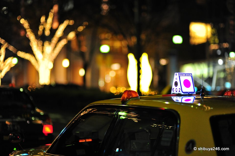 Japanese taxis always look so clean, their paint work shining, and the little logo marks on top of the car lit up make the whole scene look like an inviting bar waiting for you to enter and have one last drink on the way home after a long night out.