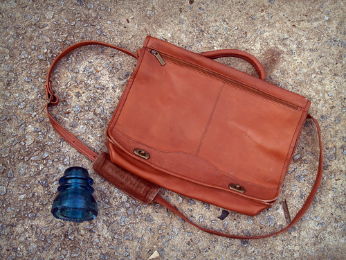glass insulator and vintage messenger bag