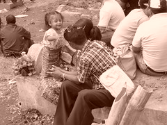 A family sitting on a grave... this little girl was so happy and cute I couldn't help taking a pic.