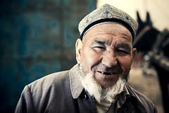 The Horse Keeper (Jeremy Snell) Tags: china horse west animal beard 50mm muslim chinese uighur xinjiang kashgar bazaar seller keeper strobist