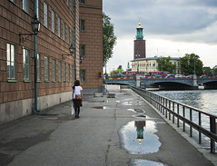 Kanslikajen After Rain (Hannes R) Tags: street city bridge windows people woman house reflection building water rain walking puddle mirror town apartments apartment sweden stockholm cityhall gamlastan puddles oldtown stadshuset kanslikajen