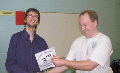 Ben receives the third-place certificate trophy from Matthew Gourlay