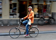 Amsterdam folder (jeremyhughes) Tags: urban orange man motion amsterdam bicycle speed cycling movement nikon cyclist sneakers cap nikkor panning folder redshoes foldingbike homme fiets flatcap orangejacket foldie d700