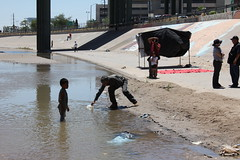 Sergio Adrian's dad Jesus Hernandez gathers water to wash his blood from the sands (Charles J. Scanlon) Tags: family children mexico killing frontera broom riogrande riobravo ciudadjuarez keko usborderpatrol sergioadrianhernandez sergioadrian usborderpatrolkilling