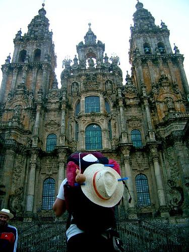 peregrina de espaldas mirando la catedral de Santiago de Compostela con la mochila a cuestas