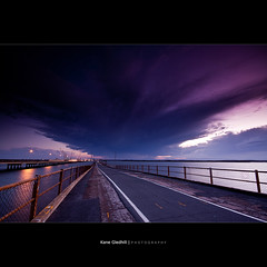 The First Storm Cloud ([ Kane ]) Tags: ocean bridge sea sky storm water clouds dusk path australia brisbane explore qld queensland kane redcliffe frontpage stormclouds gledhill 50d hornibrook kanegledhill wwwhumanhabitscomau kanegledhillphotography