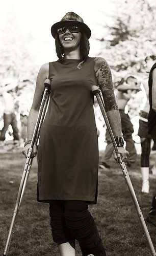A tall slender woman wearing a slip dress and an awesome hat.  She's got tattoos on one arm, and is using crutches.  She's grinning.