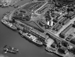 Aerial view of the Corporation Quay, 1950 (Tyne & Wear Archives & Museums) Tags: portofsunderland sunderland riverwear heritage industry industrial ships vessels quays docks corporationquay cranes coalstaithes railways tugs tugboats blackandwhitephotograph digitalimage industrialheritage maritimeheritage shipbuildingheritage abstract archives fascinating extraordinary interesting unusual northeastofengland unitedkingdom aerialview aerialphotograph june1950 portauthority riverwearcommissioners river harbour management port dock quay dredging developments construction production structure frame coaltrade alliedindustries marineengineering shiprepairing workboats vessel boat ship deck rail transportation crane chain mast chimney cylinder cargo cabin container road buildings wall roof window shadow daylight bridge crossing yard