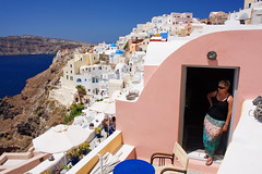(Raphael Borja) Tags: street blue sea summer woman architecture canon greek mediterranean view candid balcony skirt santorini greece doorway porch colourful oia ef1740mmf4l 40d