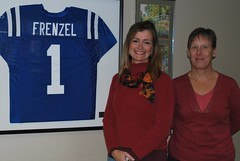 Sue Eckl and Becky Helgeland, who organize the Woodbrook Bazaar, stand in front of Tyler Frenzels Colts jersey which is located in the hall of Woodbrook Elementary School. The 2nd Annual Woodbrook Bazaar will raise money for Sunflowers in December, which was created in memory of Tyler.