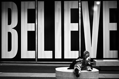 believe. (Vitaliy P.) Tags: street new york city nyc sleeping bw white man black hat sign 50mm big nikon pants baseball manhattan candid homeless letters down sneakers midtown explore cap camouflage believe gothamist asleep f18 laying explored d80 gettylicensed