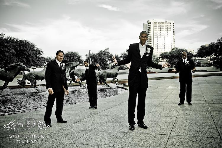 rasmi and his groomsmen doing bad boy poses at candace and rasmi's wedding reception in the las colinas plaza outside la cima club