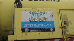 Advertising on the side of a Chicago Department of Sewers truck in traffic. Chicago Illinois. Early November 2009.