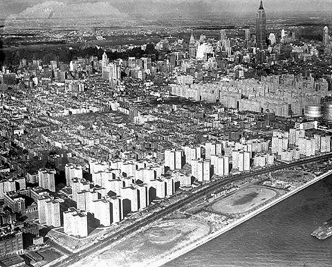 An aerial shot of Manhattan that spotlights the newly constructed wall of public housing on the East River -- Lillian Wald and Jacob Riis -- and the middle-class private city at the right, Stuyvesant Town, circa 1949.
