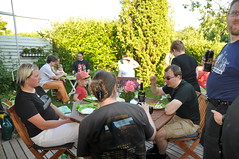 People sitting at a table and standing in the garden, eating and drinking