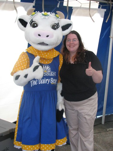 A person dressed in a cow suit wearing a daisy hat and holding her hands in a 'thumbs up', with me standing next to her grinning like a fool - I has a cow!