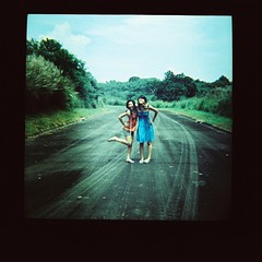 meet the crazy and the uptight (EXPLORED!) (pattyequalsawesome) Tags: road street blue girls friends sky people black green 120 film nature grass kids clouds self crazy lomo xpro lomography crossprocessed sister philippines squareformat manila dianaf mika 2009 kodakektachromee200