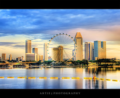 The Singapore Flyer :: HDR (Artie | Photography :: I'm a lazy boy :)) Tags: city sea reflection water skyline clouds marina photoshop sunrise canon buildings singapore cs2 tripod kitlens explore wharf 1855mm frontpage efs barrage hdr artie marinabay 3xp photomatix tonemapping tonemap 400d marinabarrage rebelxti singaporeflyer