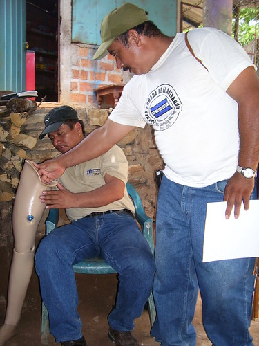 Armando and Jose discussing a prosthetic leg adjustment needed by a member of the Ilobasco Association of Disabled Persons