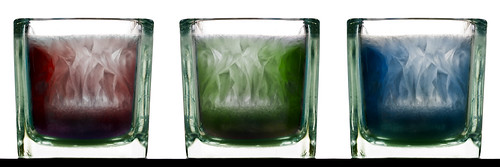 A triptych of a glass candle holder containing different coloured wax