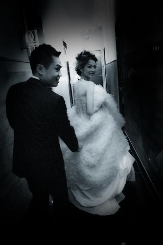 新郎牽著新娘的裙襬要進房換下一套禮服,新娘開心地回頭想要留下一張照片。