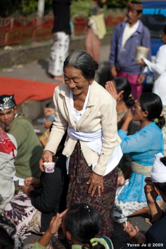 這位婆婆正在幫拜拜的人群頭上黏米