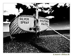 silver spray, shot at Aldburgh in Suffolk (liam black ( needing inspiration )) Tags: ocean old sea sky water clouds silver boats seaside sand pebbles rope spray milfordhaven rowingboat