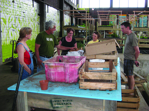 Milwaukee residents learn about seeding sprouts on a Sweet Water tour with James Godsil.  ~photo Casey Twanow
