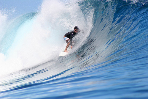 Dennis Tihara surfing the waves at Teahupoo, Tahiti. / Nisa + Ulli Maier