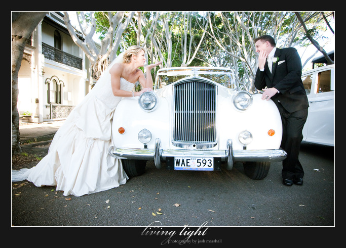 Bride and groom blow a kiss on fig lined streets. Newcastle wedding photography.