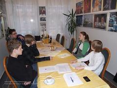 fünf Leute sitzen an einem Tisch und reden