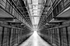 Contrasted Confinement (Surrealize) Tags: alcatraz sanfrancisco california bars steel light bay prison therock grit harsh bw surrealize hdr nikon d700 wideangle jail hallway hall illumination contrast detail grid black white solitary confinement hope cell block freedom entrapment escape federal penitentiary angle leading lines symmetry monochrome island bampw artinbw