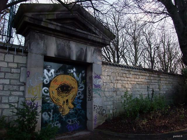 Une porte d'entrée du Père Lachaise, soigneusement décorée d'un graffiti