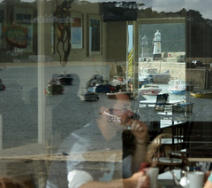 Reflected (farwest56) Tags: uk england people lighthouse holiday man reflection building cup window glass table boats restaurant cafe chair cornwall drink harbour eating drinking quay wharf stives cafewindow a350