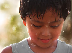 in the rain (alvin lamucho ) Tags: park boy cute water rain garden droplets drops kid dof bokeh adorable handsome son telephoto jed raindrops kuwait depth waterdroplets goodlooking 200mm mahboula eldest abuhalifa canon450d alvinlamucho