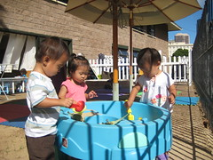 Aki playing in the sand table with new friends