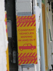 Signs at the entrance to the First Choice car wash illustrated problems with having an auto-oriented business in a pedestrian zone. Photo by Jason.