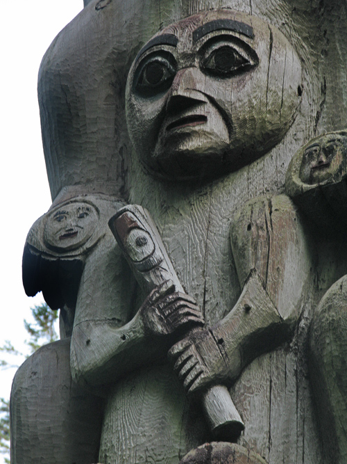 human figure holding a flute on a totem pole in Kasaan Totem Park, Kasaan, Alaska