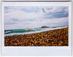 Swimmers (AndyWilson) Tags: girls film beach clouds brighton fuji wide shingle pebbles westpier instant 100 swimmers wonky instax pad2009 igotwetshootingthis iwasclosertotheseathanitlooks layingfacedownonpebbles thenwavegotme