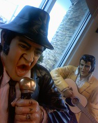 Faux Belushi attempts to eat a golden ice cream cone while Elvis watches