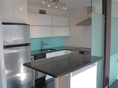 Modern Kitchen Designed with a Back Painted Glass BackSplash Installed, complimenting the sandblasted Glass Wall