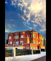let the sunshine in! - kuwaiti villa [hdr] (alvin lamucho ©) Tags: blue sky orange sun sunlight house home sunshine architecture clouds fence golden rich perspective arab villa mansion kuwait wealthy neighbor hdr kuwaiti letthesunshinein runrays canon450d alvinlamucho