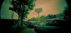 Planet billboard and cars (khai_nomore) Tags: 120 film mediumformat ambientlight pinhole petalingjaya rm photoexhibition 2minutes soloexhibition mutiaradamansara fujifilmreala100 f132 autaut filmforever holga120wpc homegrownspace filmindulge