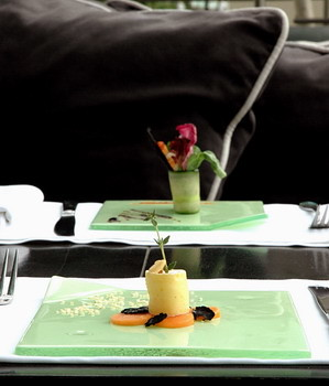 Contemporary glass dinnerware with green glass dish for amuse bouche or dessert presentation