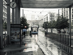 Rainy Day at Sickla Kaj (Hannes R) Tags: street city trees people woman reflection clock water rain station umbrella reflections puddle mirror town time sweden stockholm tram a32 hammarby sickla hammarbysjstad sicklakaj tvrbanan flexityswift flexity sjstan