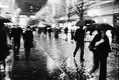 Untitled (HAMED MASOUMI) Tags: street uk man black film wet rain analog umbrella canon walking manchester women iso400 f14 piccadilly ground negative iranian a1 hamed citycentre   masoumi hamedmasoumi   legacypro lifegoesonhere
