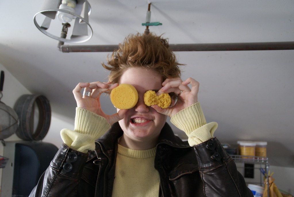 A student holds two sponges over their eyes