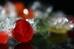 under wraps:  263/365 (helen sotiriadis) Tags: red orange white black macro reflection green yellow closeup canon dof candy sweet bokeh hard depthoffield clear 365 transparent wrapper cellophane canonef100mmf28macrousm canoneos40d toomanytribbles