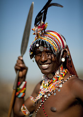 Samburu warrior with beaded ornaments holding a spear - Kenya (Eric Lafforgue) Tags: africa portrait people man smile face hat happy beads dof kenya african culture tribal human chapeau tribes bead warrior afrika remote tradition tribe ethnic moran samburu tribo jewel homme visage spear headdress afrique headwear ethnology headgear tribu eastafrica beadednecklace 5504 coiffe qunia lafforgue ethnie morane ethny  qunia    beadsnecklace kea    a